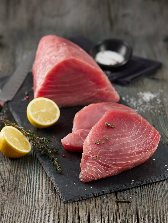 Frische Thunfisch-Steaks in Center-Cut Qualität auf dunkler Steinplatte angerichtet mit Zitronenscheiben und Rosmarin